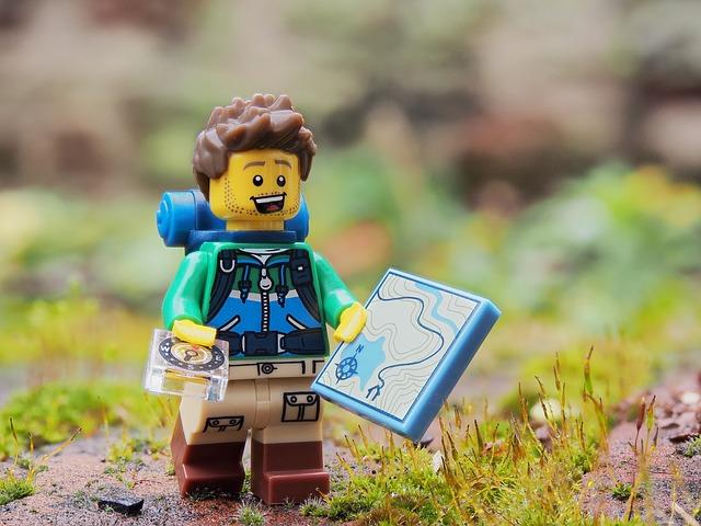 Lego figurine of a hiker holding a map.