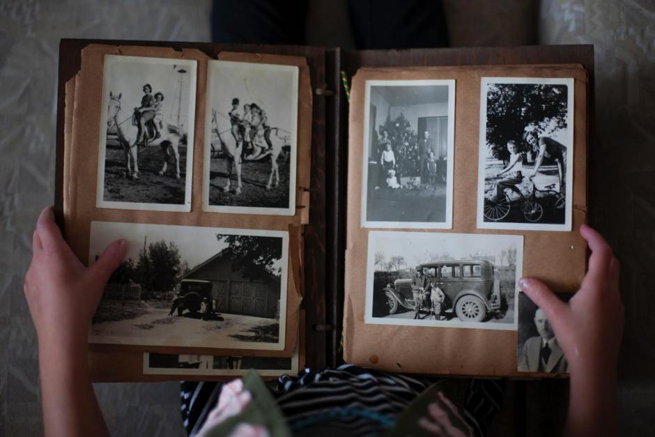 Overhead view of child holding old photo album open in their lap.